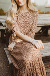 The Elena Patterned Tiered Dress in Nude, lifestyle shoot; sitting front view