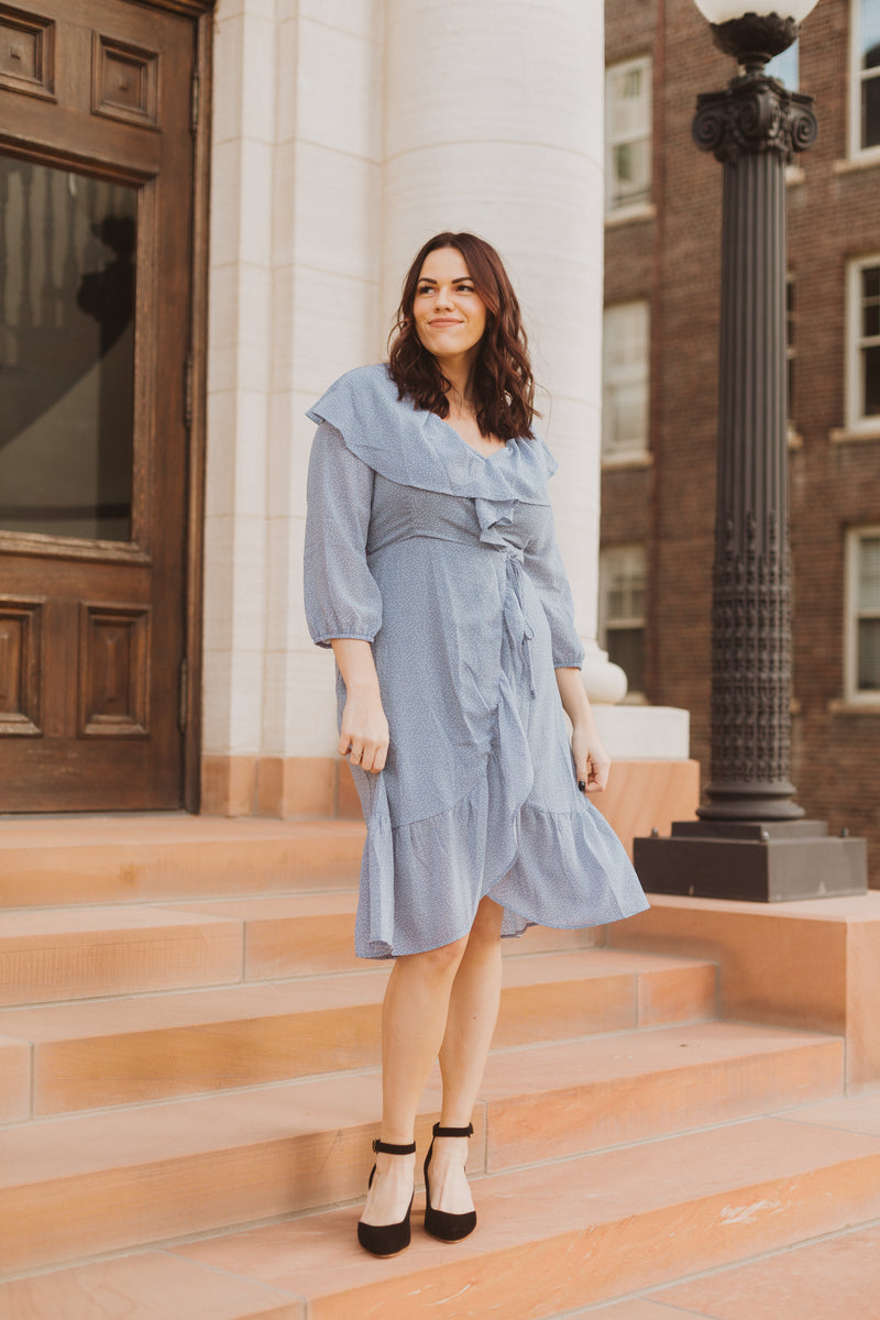 The Vinnie Ruffle Wrap Dress in Powder Blue, lifestyle shoot; front view