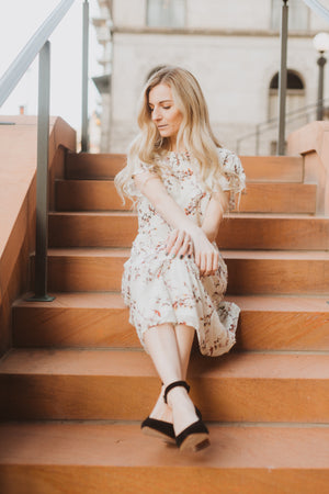 Piper & Scoot: The Mildred Floral Empire Dress in Cream, lifestyle shoot; sitting front view
