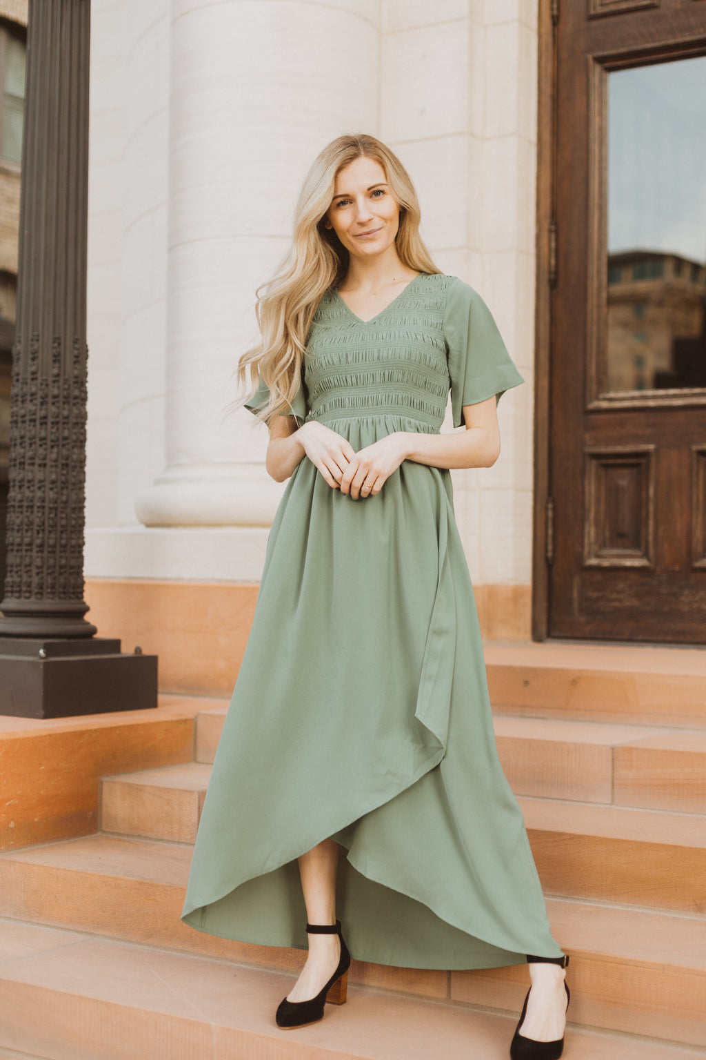 The Fancy Flutter Sleeve Dress in Sage, lifestyle shoot; front view