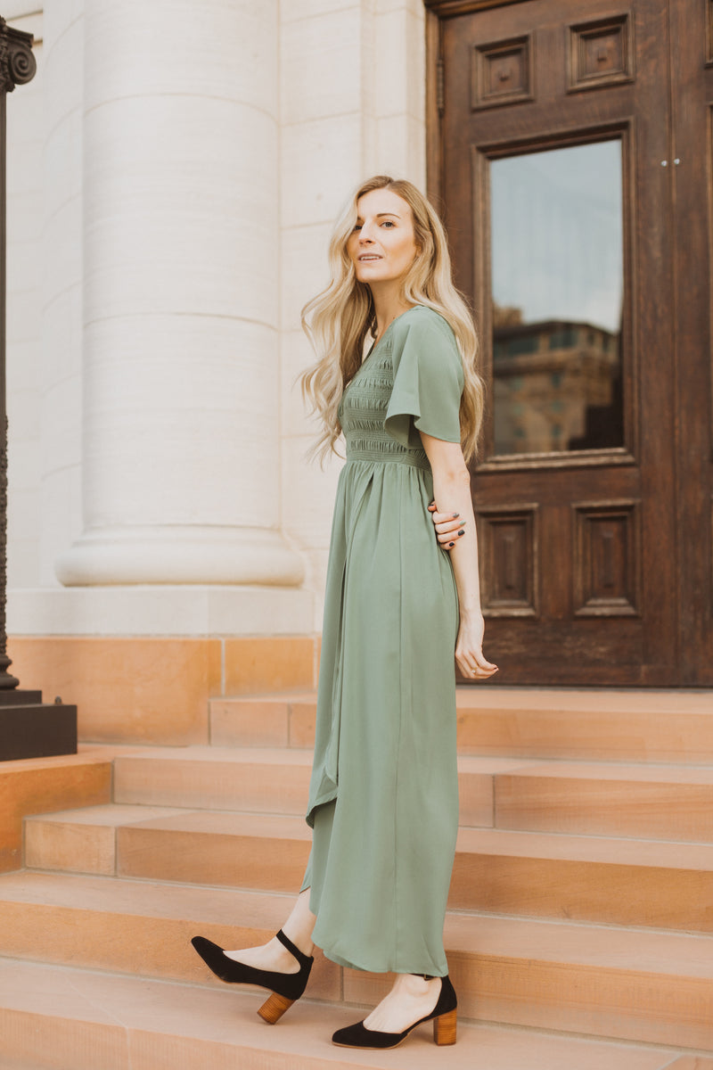 The Fancy Flutter Sleeve Dress in Sage, lifestyle shoot; side view