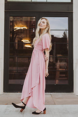 The Fancy Flutter Sleeve Dress in Blush, lifestyle shoot; side view