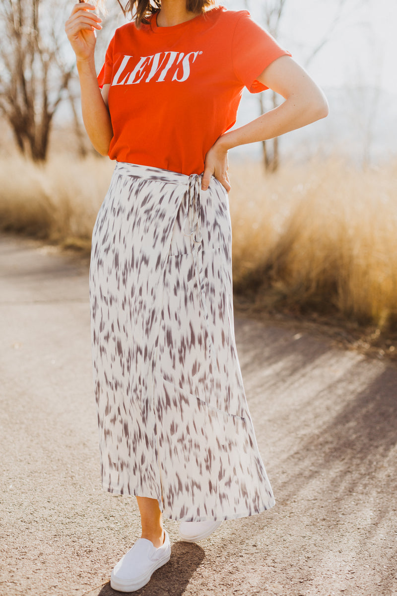 The Merrick Strokes Wrap Skirt in White, lifestyle shoot; side view