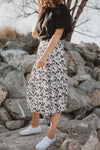 The Willa Floral Pleated Skirt in White, lifestyle shoot; side view