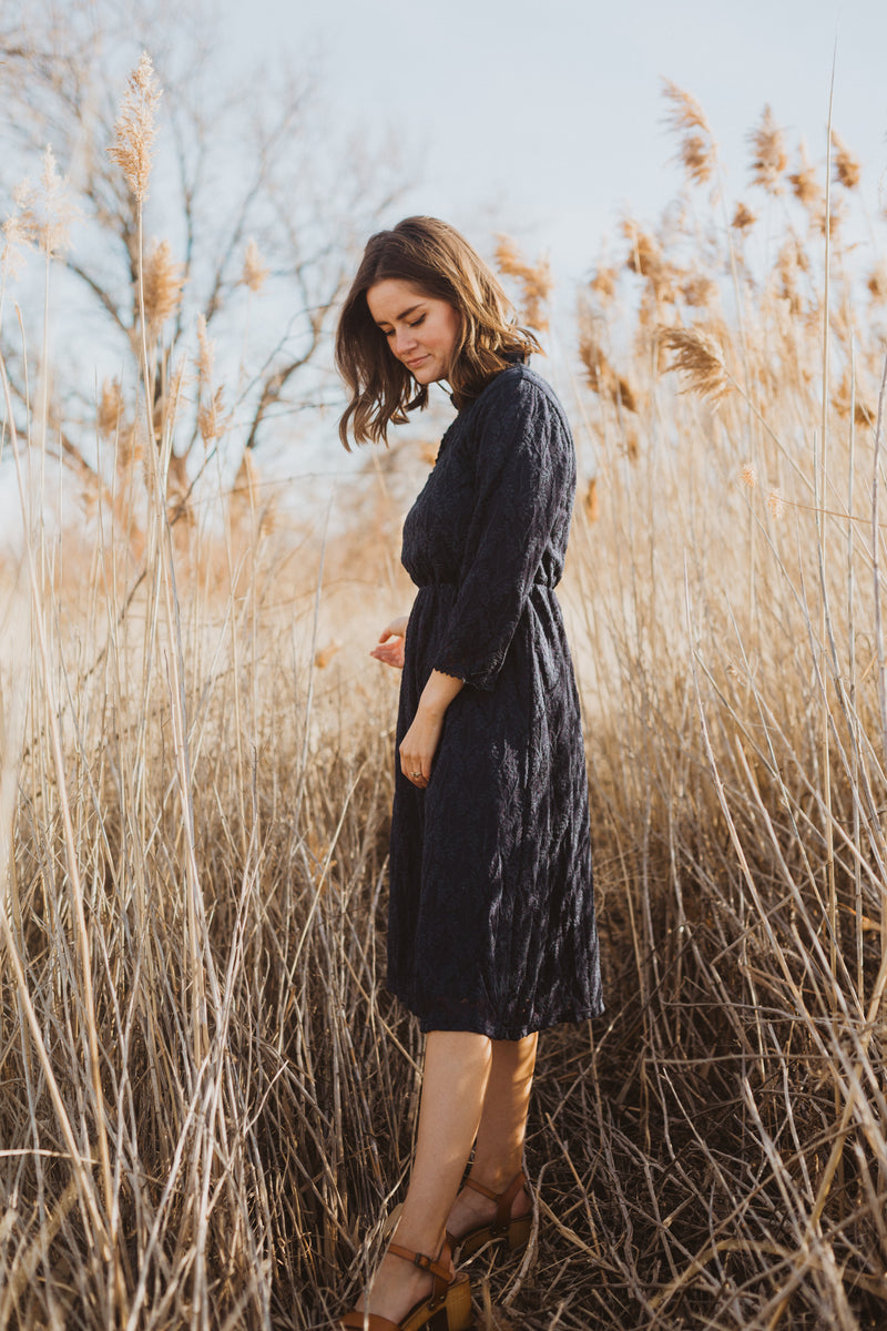 The Othello Lace Ruffle Dress in Navy, lifestyle shoot; side view