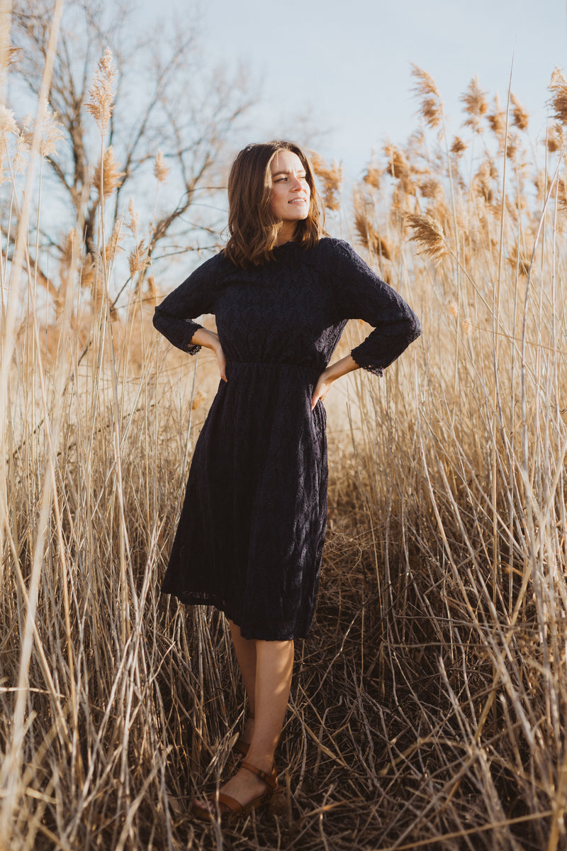 The Othello Lace Ruffle Dress in Navy, lifestyle shoot; front view