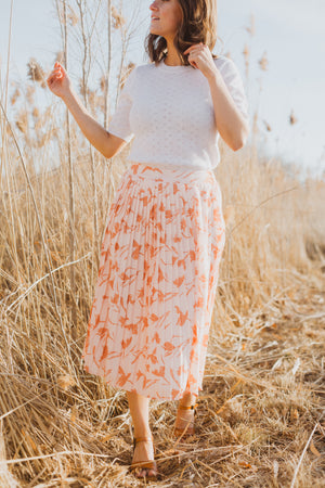 The Jenna Floral Pleated Skirt in Blush, lifestyle shoot; front view
