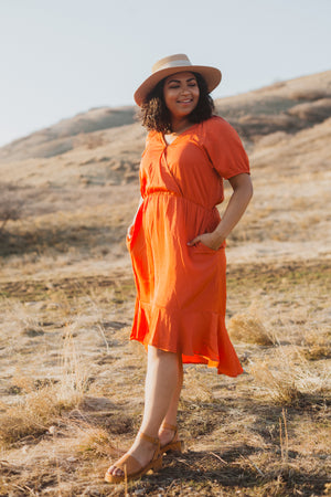 The Ingrid Ruffle Dress in Tangerine, lifestyle shoot; front view