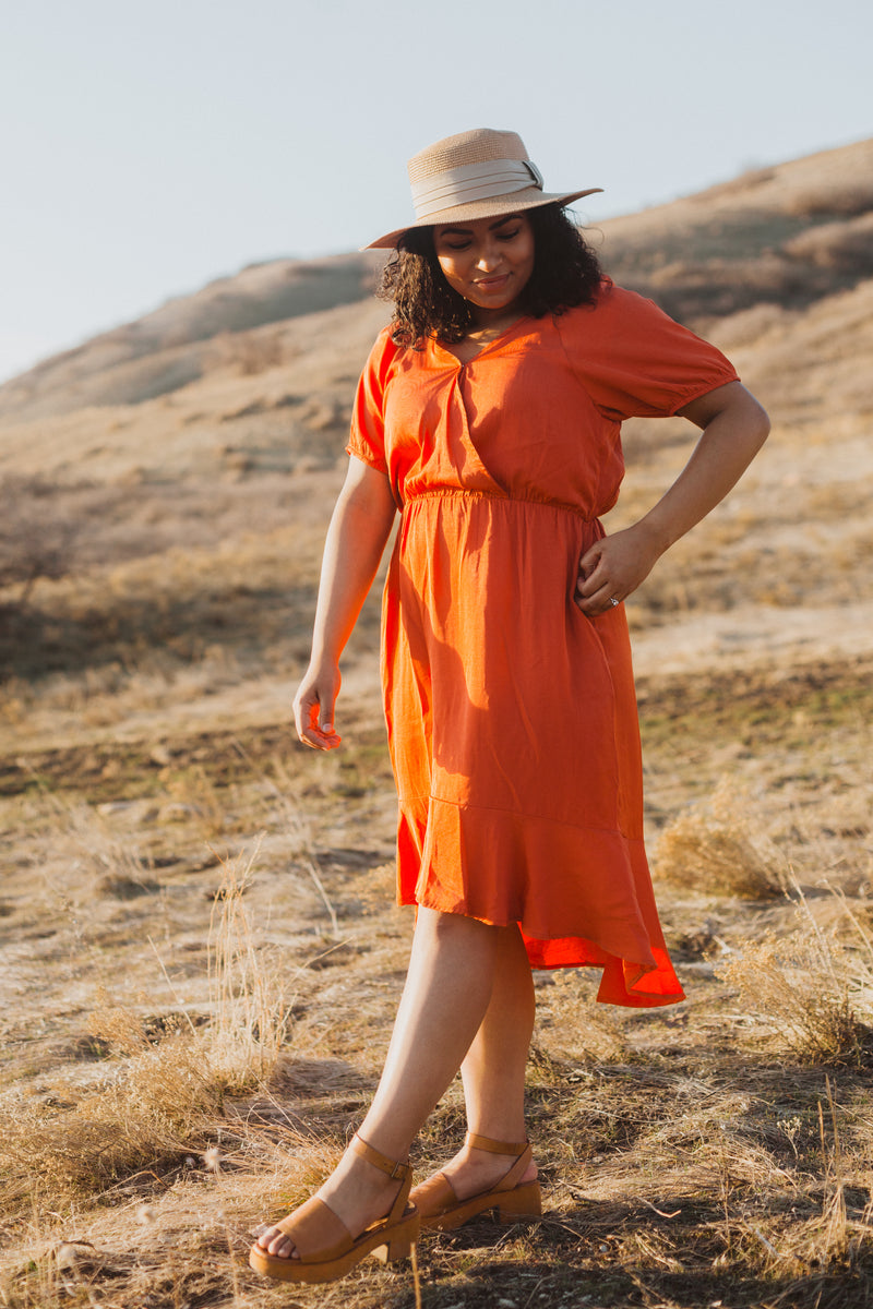 The Ingrid Ruffle Dress in Tangerine, lifestyle shoot; side view
