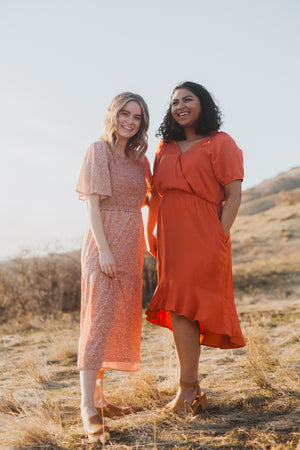 The Ingrid Ruffle Dress in Tangerine, lifestyle shoot; front view paired with friend
