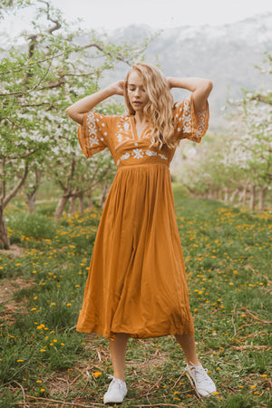 The Cadence Embroidered Detail Dress in Golden, lifestyle shoot; front view