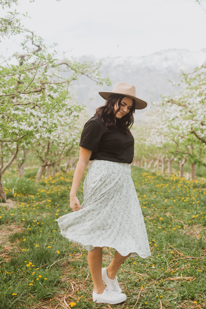 The Emely Floral Midi Skirt in Sage, lifestyle shoot; front view