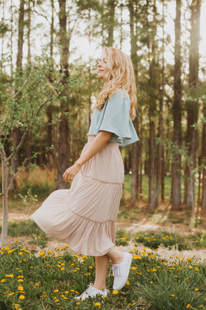 he Helena Tiered Midi Skirt in Taupe, lifestyle shoot; side view