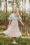 he Helena Tiered Midi Skirt in Taupe, lifestyle shoot; front view