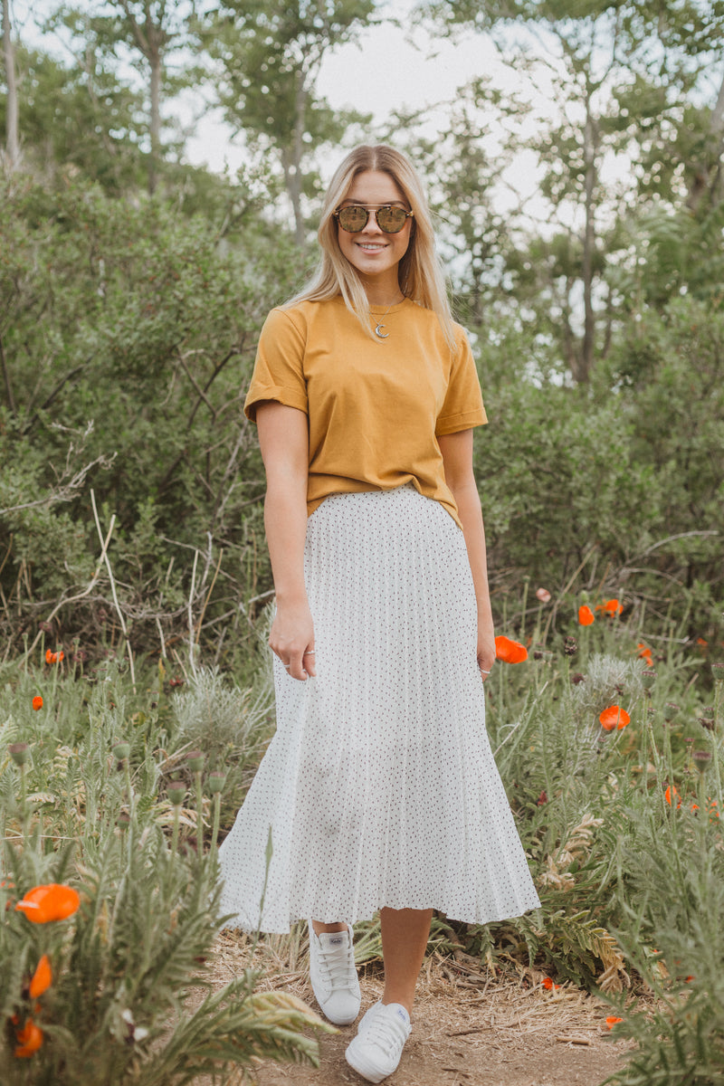 The Coleman Dot Pleated Maxi Skirt in White, lifestyle shoot; front view