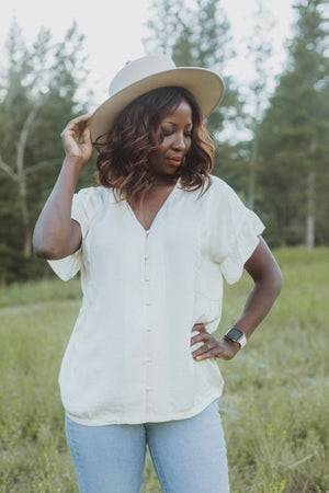 The Ari Button Ruffle Blouse in Cream, lifestyle shoot; front view