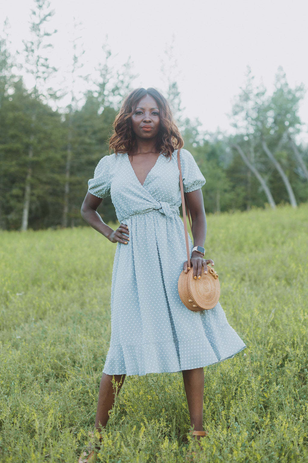 The Adaline Swiss Dot Wrap Dress in Dusty Blue, lifestyle shoot; front view