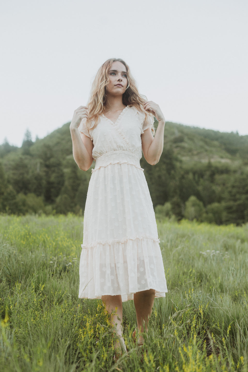 The Ember Dot Wrap Dress in Ivory, lifestyle shoot; front view