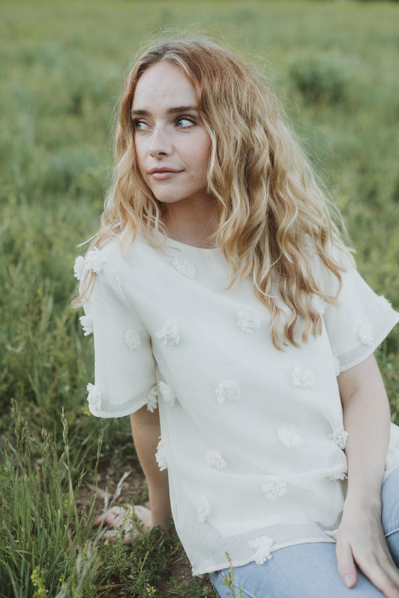 The Austin Textured Blouse in Cream, lifestyle shoot; front view