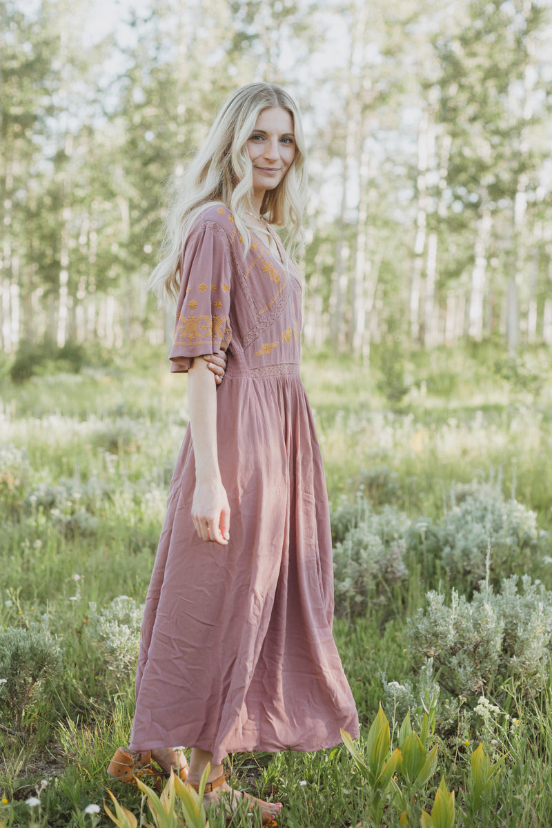 The Cadence Embroidered Detail Dress in Mauve, lifestyle shoot; side view