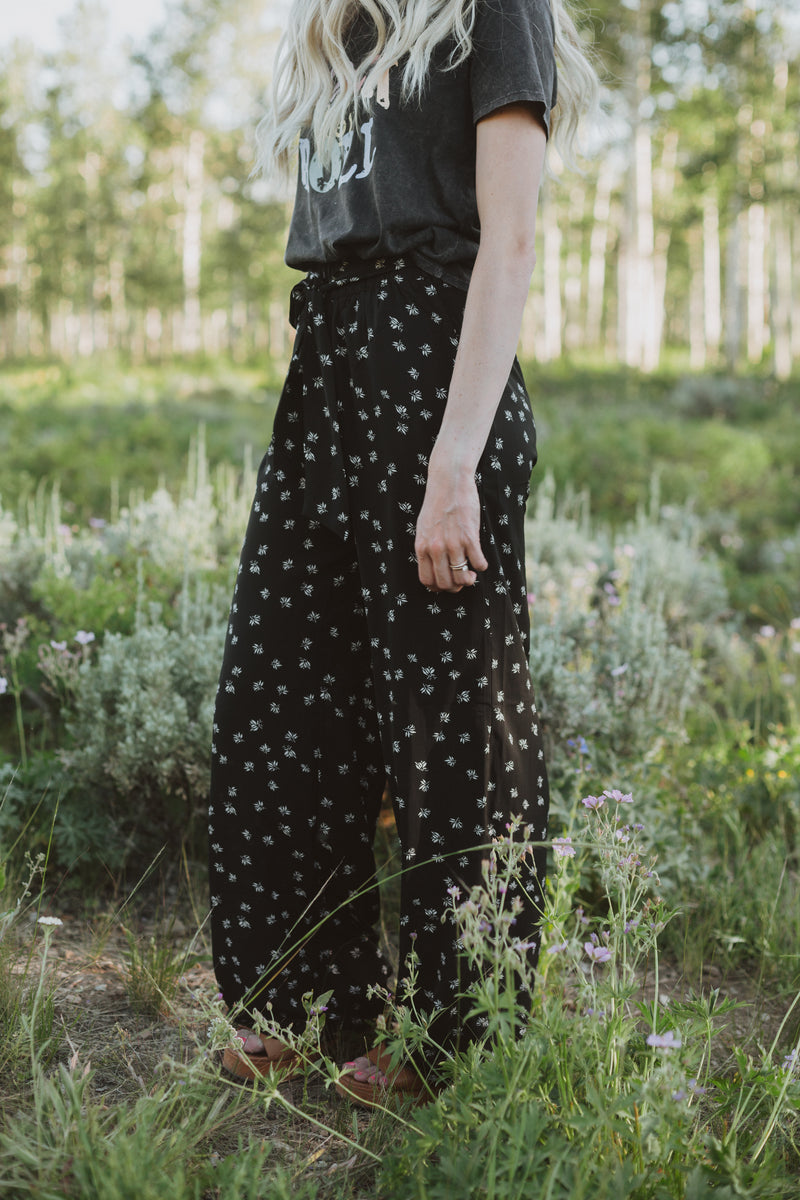 The Corbin Printed Wide Leg Trouser in Black, lifestyle shoot; side view