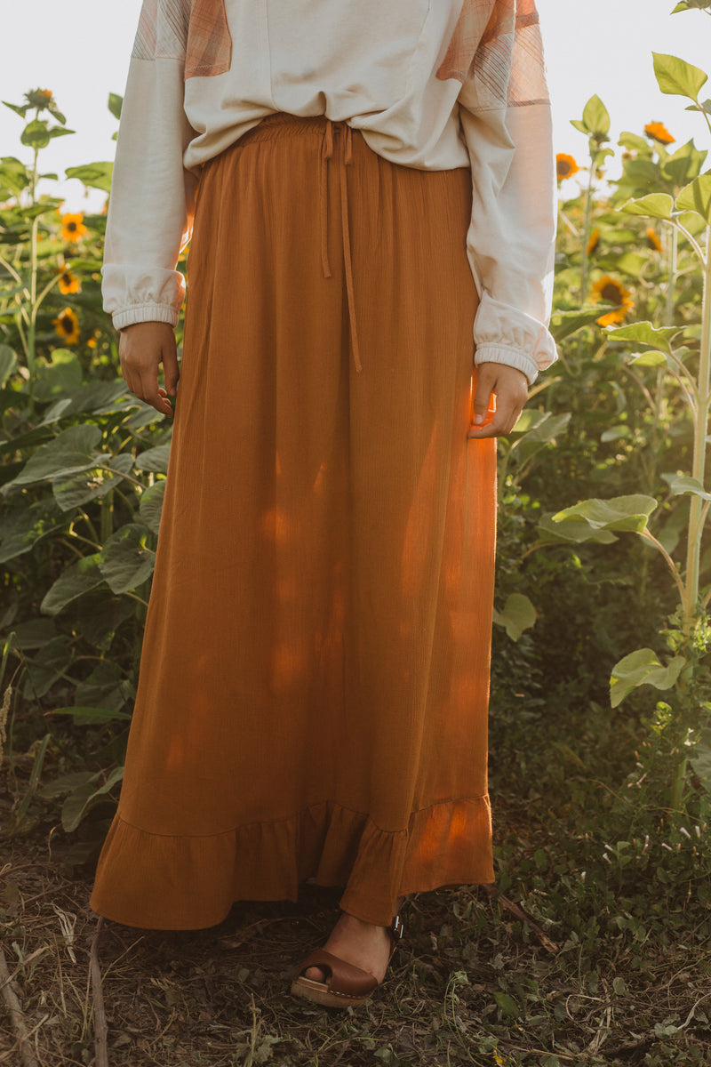 The Roddick Ruffle Maxi Skirt in Camel, lifestyle shoot; front view