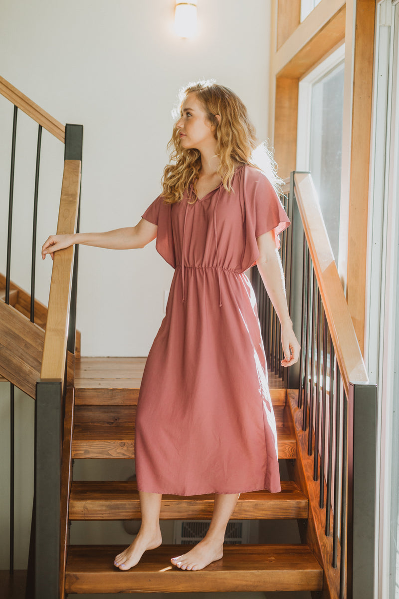 The Katee Ruffle Empire Dress in Mauve, lifestyle shoot; front view