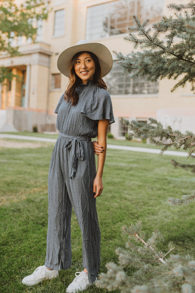 The Grier Swiss Dot Ruffle Jumpsuit in Dusty Blue, lifestyle shoot; front view