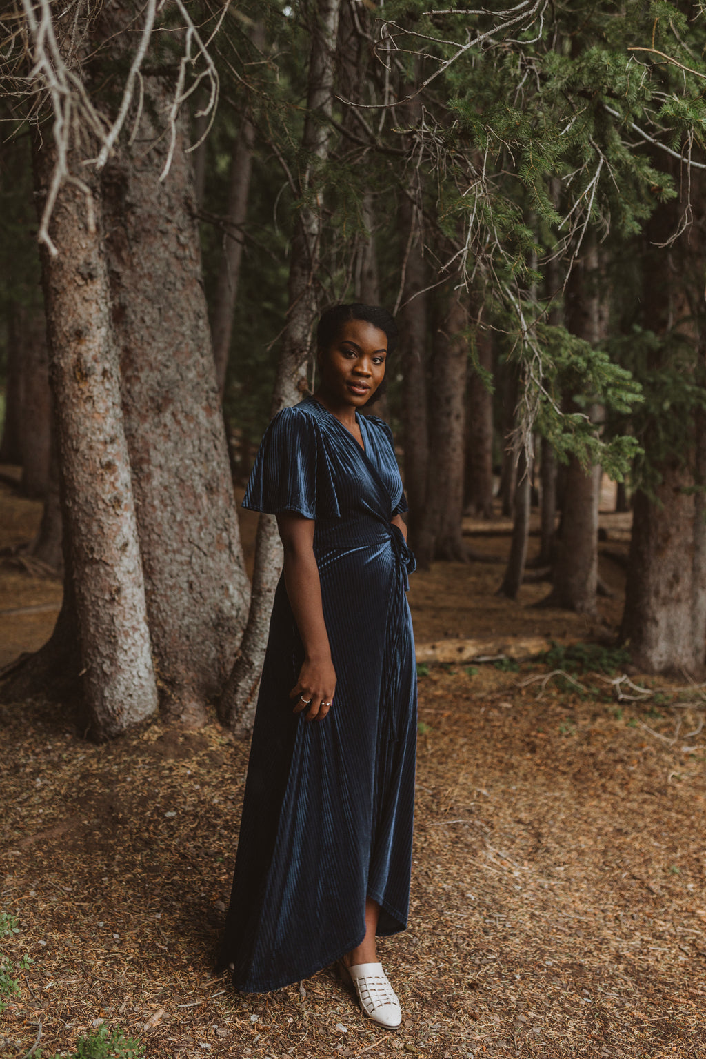 The Banton Pleated Velvet Maxi Dress in Navy, lifestyle shoot; front view