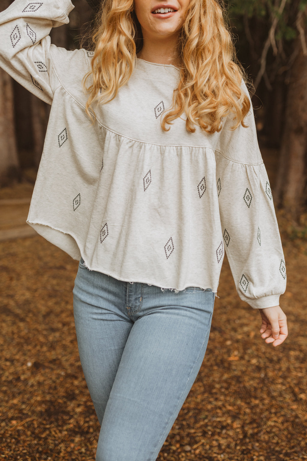 The Howe Embroidered Empire Blouse in Ivory, lifestyle shoot; front view