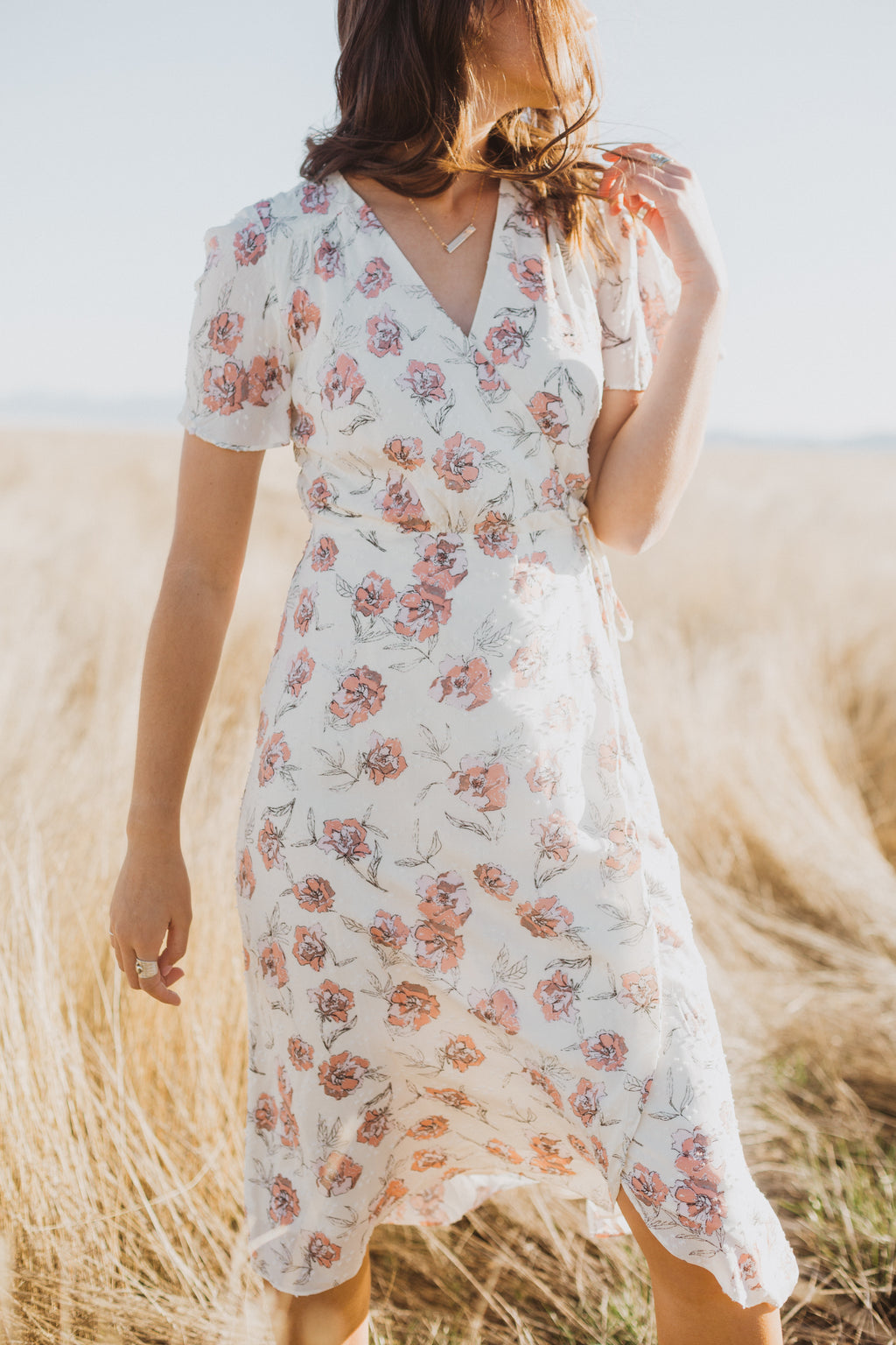 The Tiana Floral Wrap Dress in White, lifestyle shoot; front view