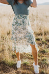 The Louisa Floral Ruffle Skirt in Natural, lifestyle shoot; front view
