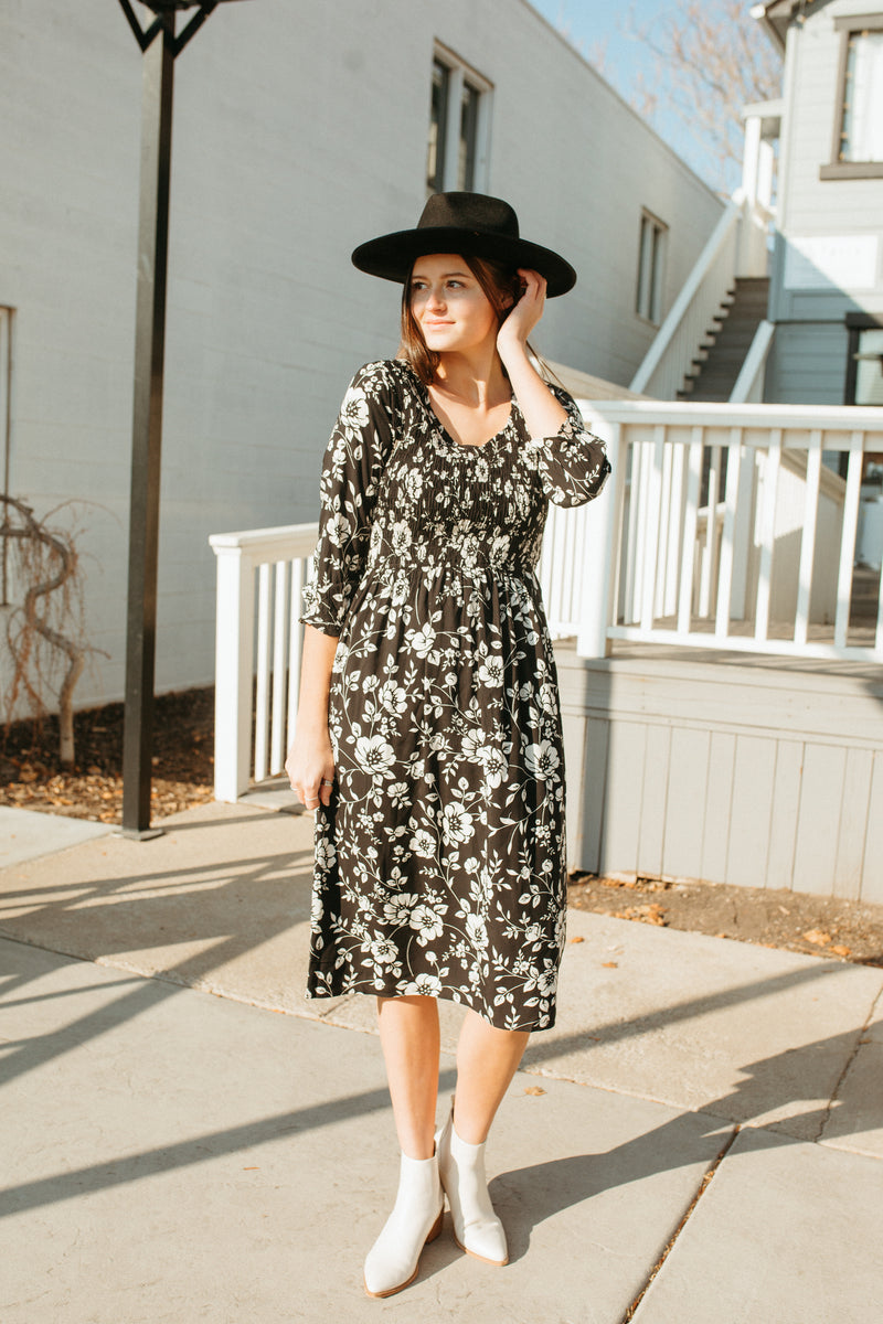 The Annie Smocked Floral Dress in Black, lifestyle shoot; front view