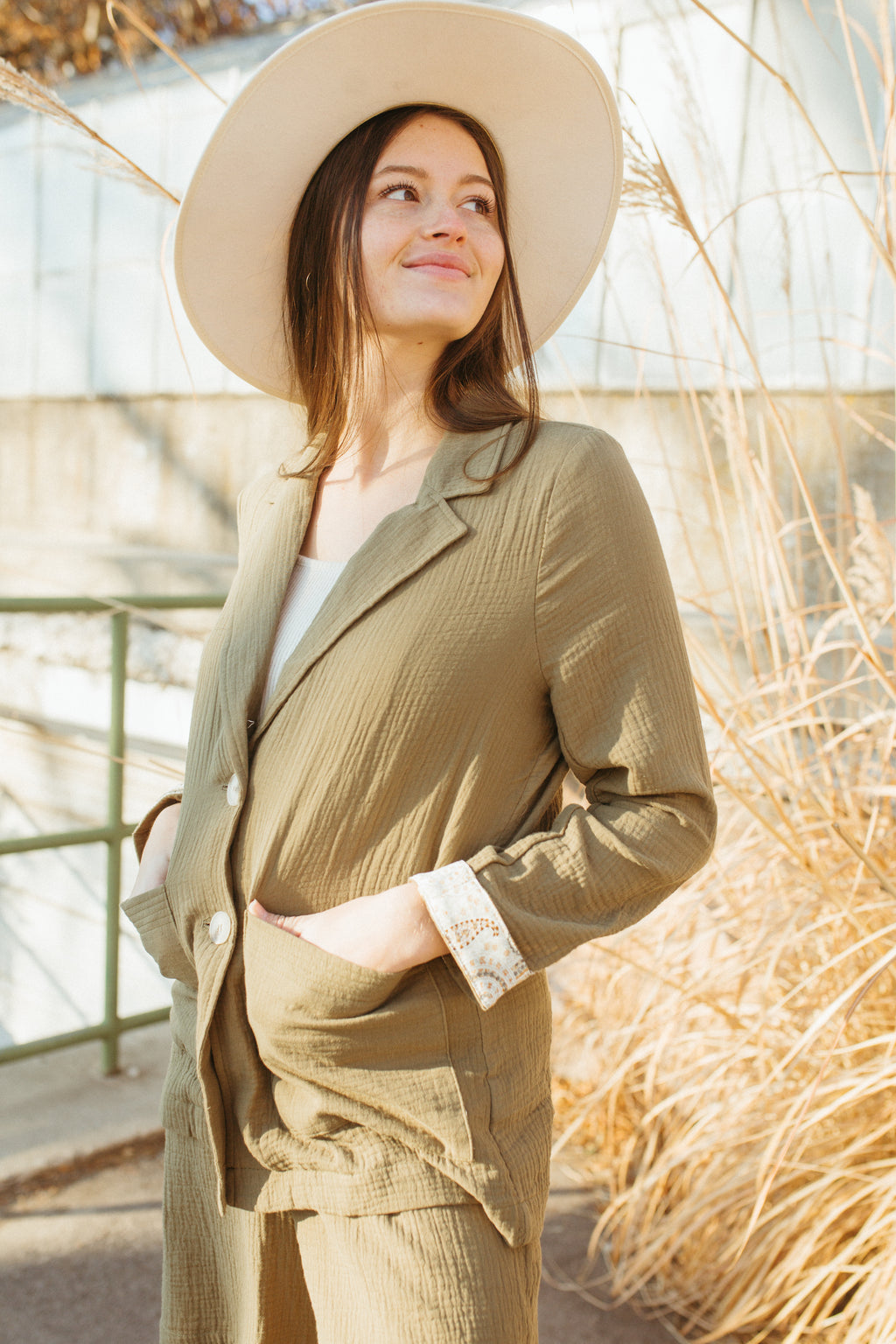 The Halle Relaxed Button Up Blazer in Olive, lifestyle shoot; side view