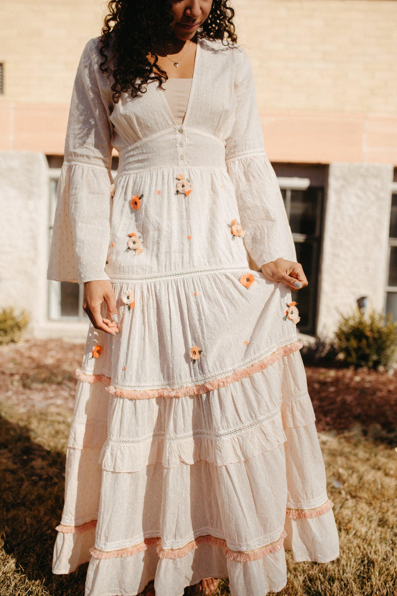 The Poppy Embroidered Maxi Dress in Creamy Blush, lifestyle shoot; front view