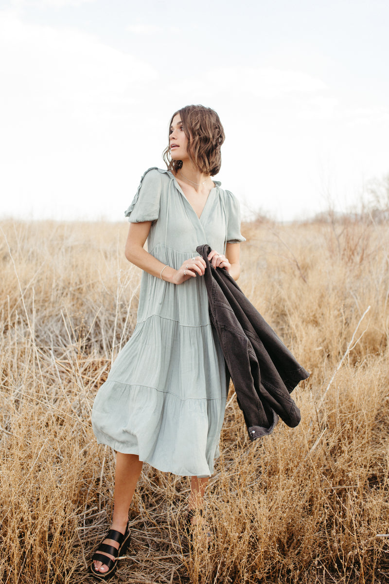 The Nadia Ruffle Detail Dress in Sage, lifestyle shoot; front vie