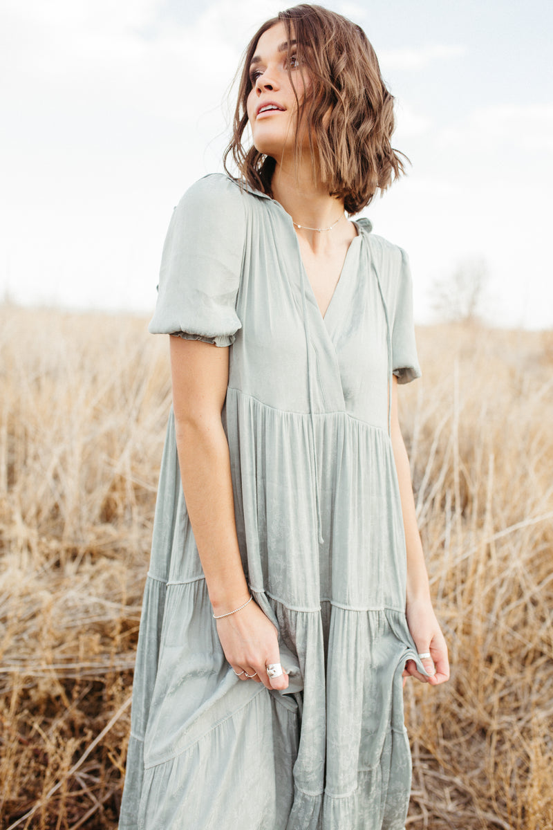 The Nadia Ruffle Detail Dress in Sage, lifestyle shoot; back view
