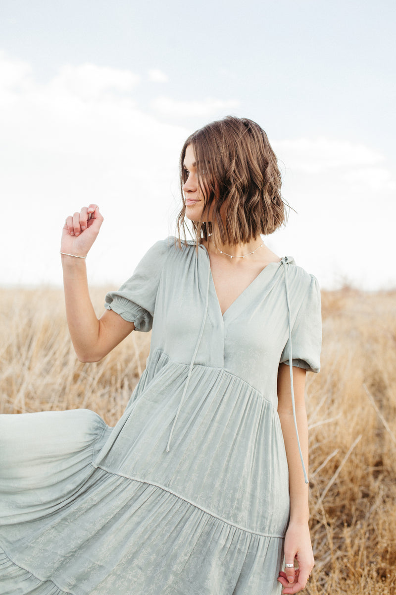 The Nadia Ruffle Detail Dress in Sage,lifestyle shoot; front vie