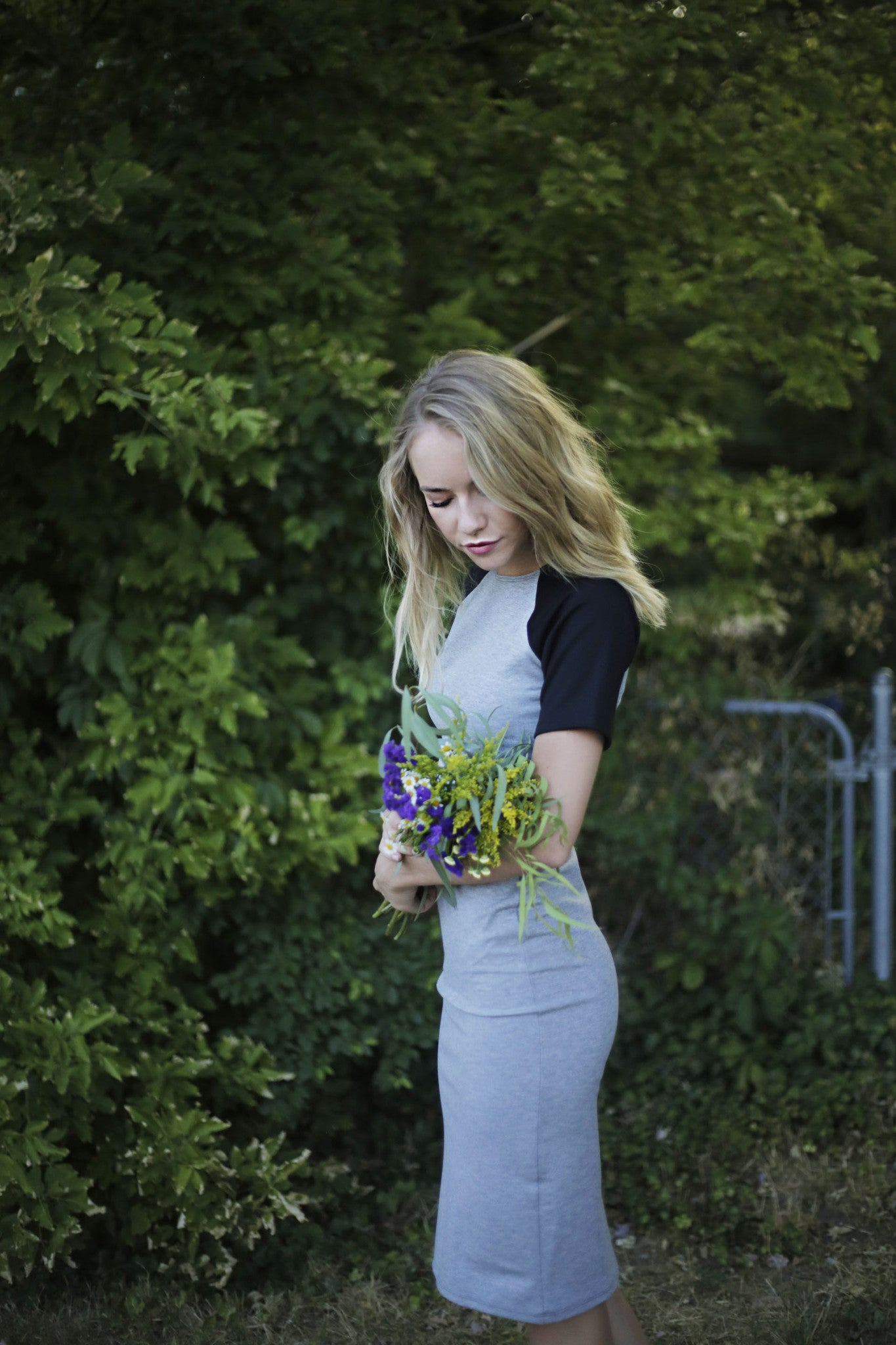 Model holding flowers and wearing charlie dress