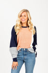 The Flex Colorblock Sweater in Peach + Navy, studio shoot; front view