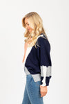 The Flex Colorblock Sweater in Peach + Navy, studio shoot; side view