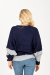 The Flex Colorblock Sweater in Peach + Navy, studio shoot; back view