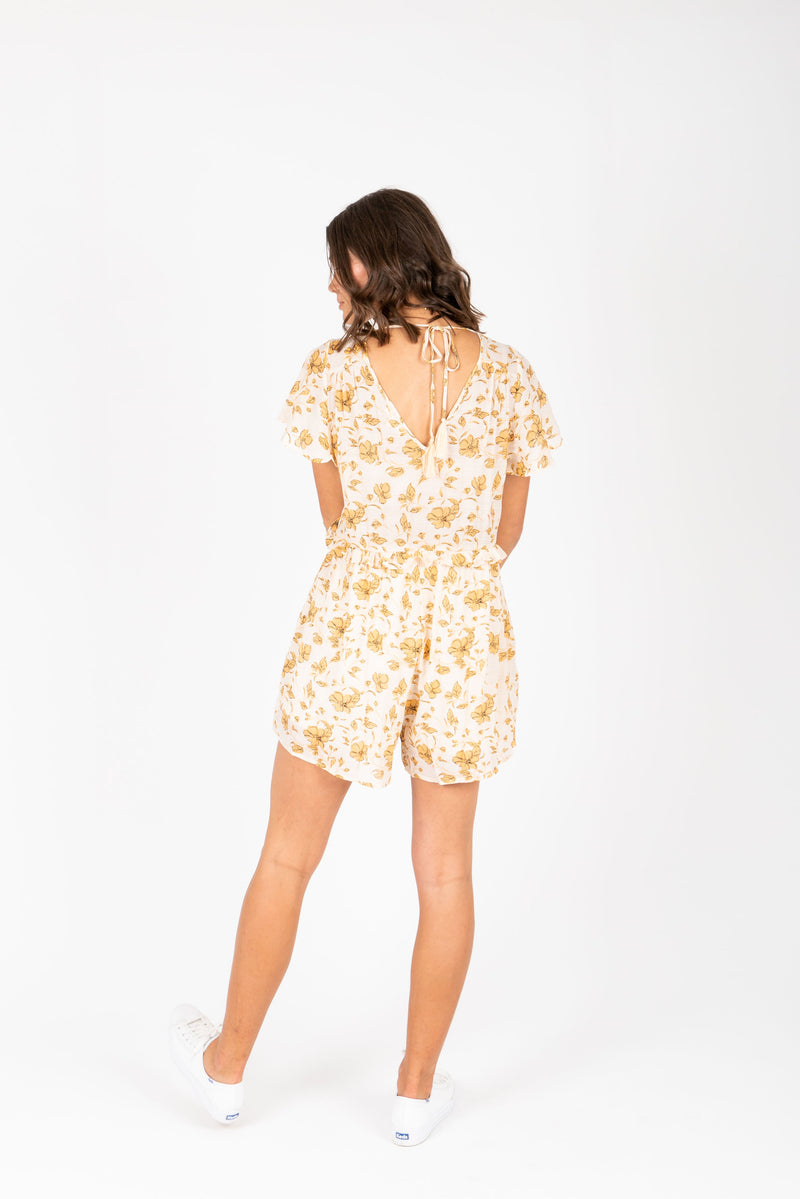 The Alexis Floral Romper in Peach, studio shoot; back view