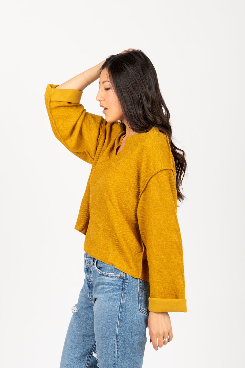 The Chief Slit Sweater in Mustard, studio shoot; side view