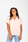 The Ari Button Ruffle Blouse in Blush, studio shoot; front view