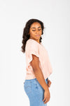 The Ari Button Ruffle Blouse in Blush, studio shoot; side view
