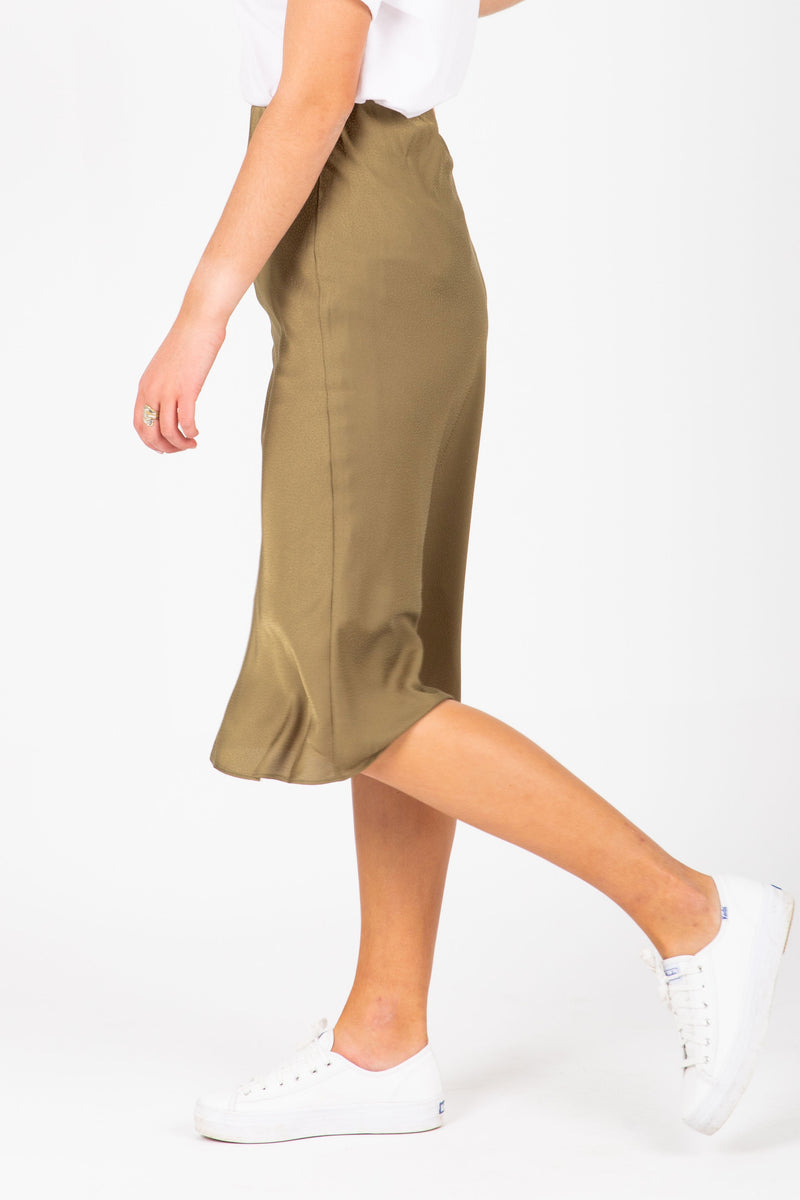 The Esme Satin Midi Skirt in Moss, studio shoot; side view