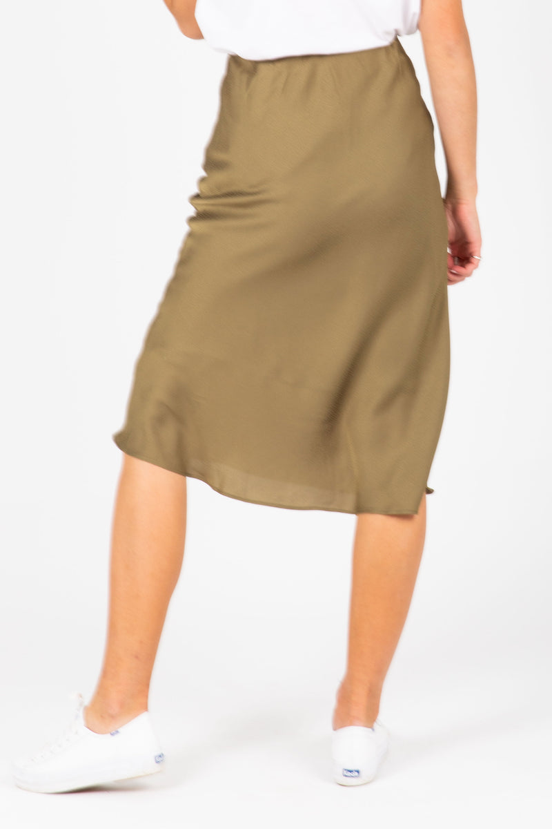 The Esme Satin Midi Skirt in Moss, studio shoot; back view