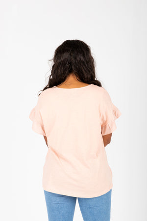 The Ari Button Ruffle Blouse in Blush, studio shoot; back view