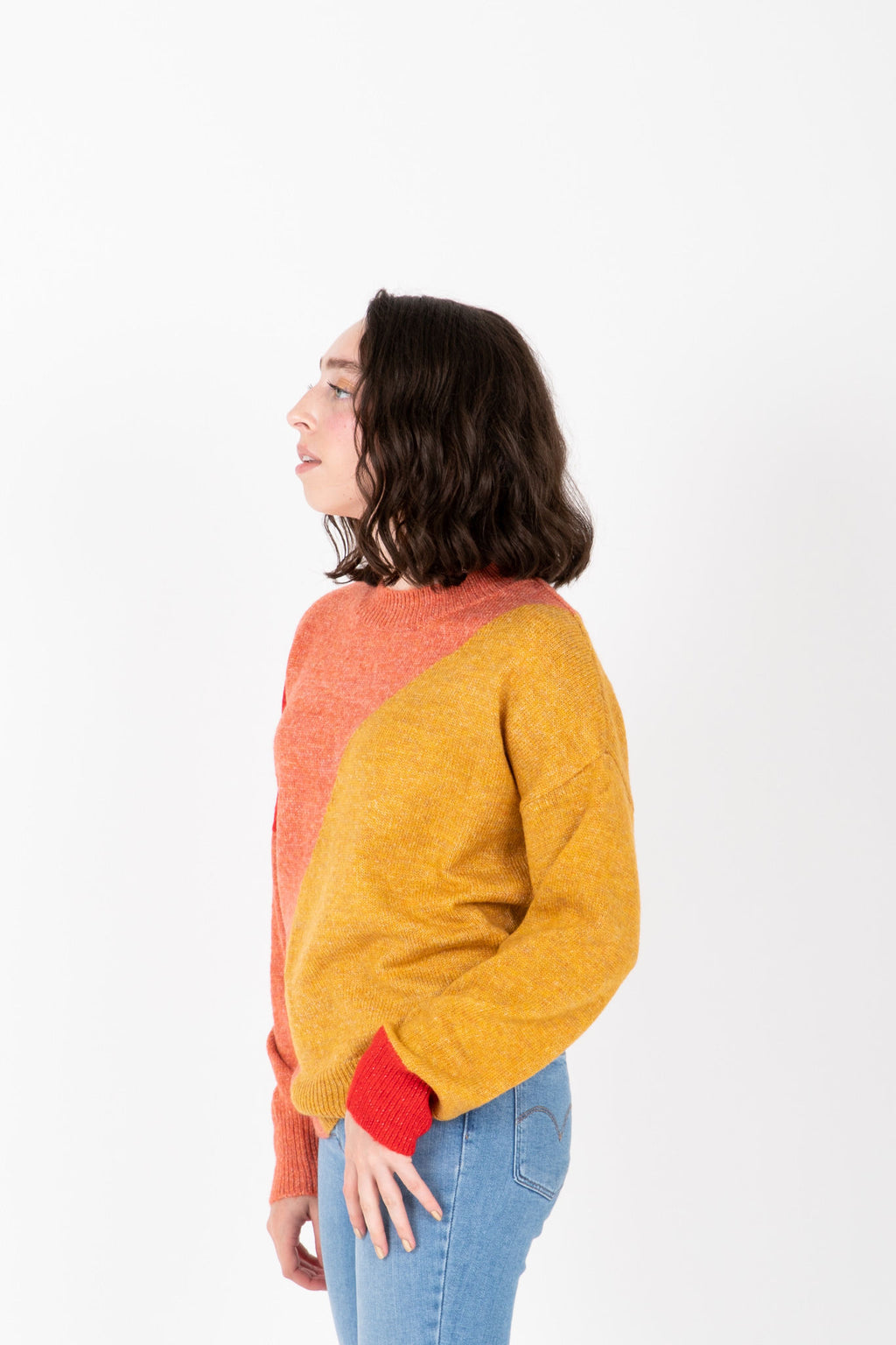 The Siren Colorblock Sweater in Mustard + Pink, studio shoot; side view
